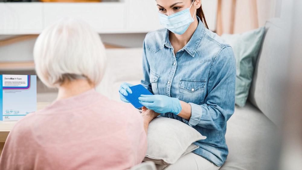 caregiver applies antimicrobial foam dressing